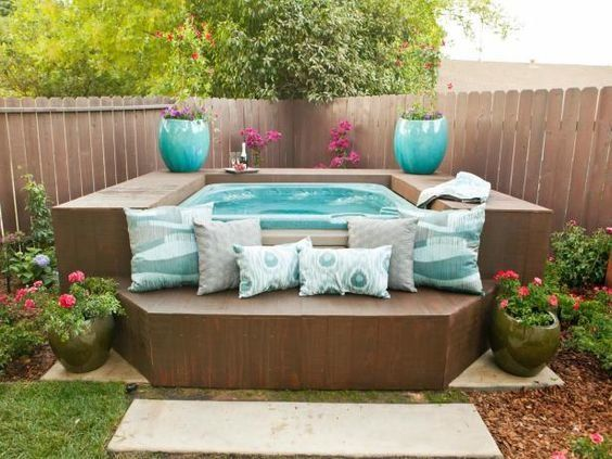 DIY backyard hot tub enclosure idea - love the use of the blue flower pots and pillows for that pop of color.  Gorgeous!