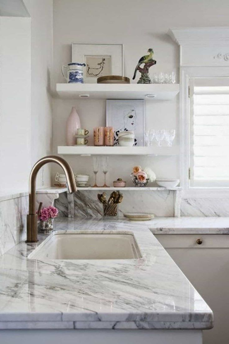 Kitchen Designed With Marble Countertops And Undermount Sink With Bronze  Faucet