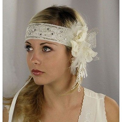 I love this look, with a thick headband and a knot of flowers, feathers, ribbons to the side.