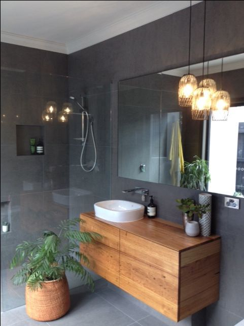 Timber vanity unit in a dark tiled bathroom