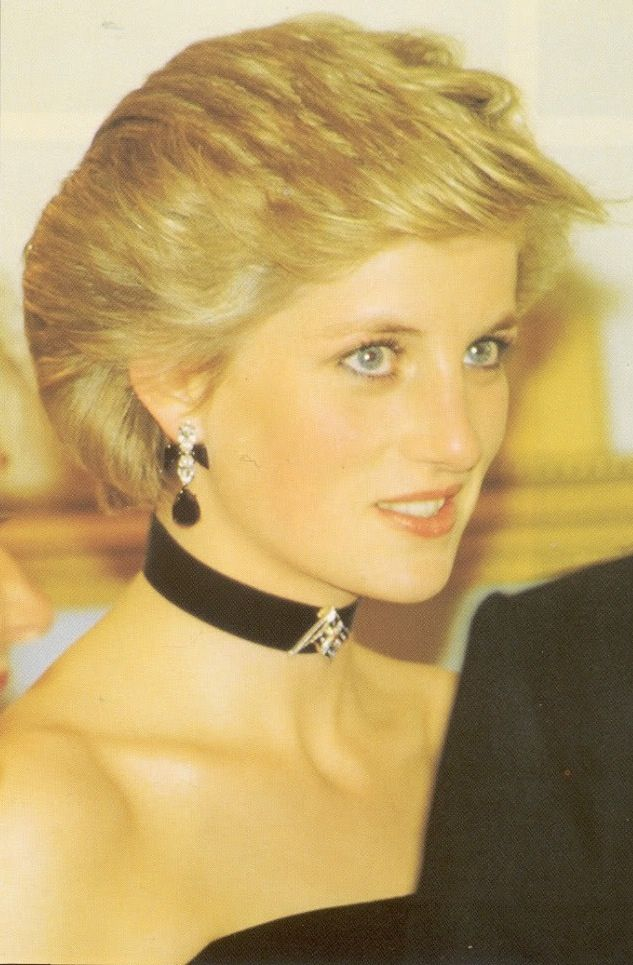 Diana wore this black ribbon choker with a small diamond brooch pinned on it when she visited Spain in 1987. The drop earrings are from her costume collection of jewelry and are made with colored crystals.