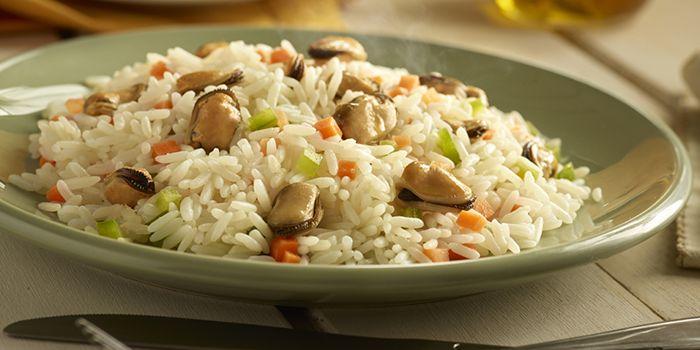 En una olla con aceite, freír la cebolla picada, agregar la zanahoria rallada y el pimentón picado. Luego, agregar el arroz y freír todo por 2 min, revolviendo constantemente. A continuación, agregar los choritos, 4 tazas de agua hirviendo y la sal. Tapar y cocinar a fuego lento por 20 min.