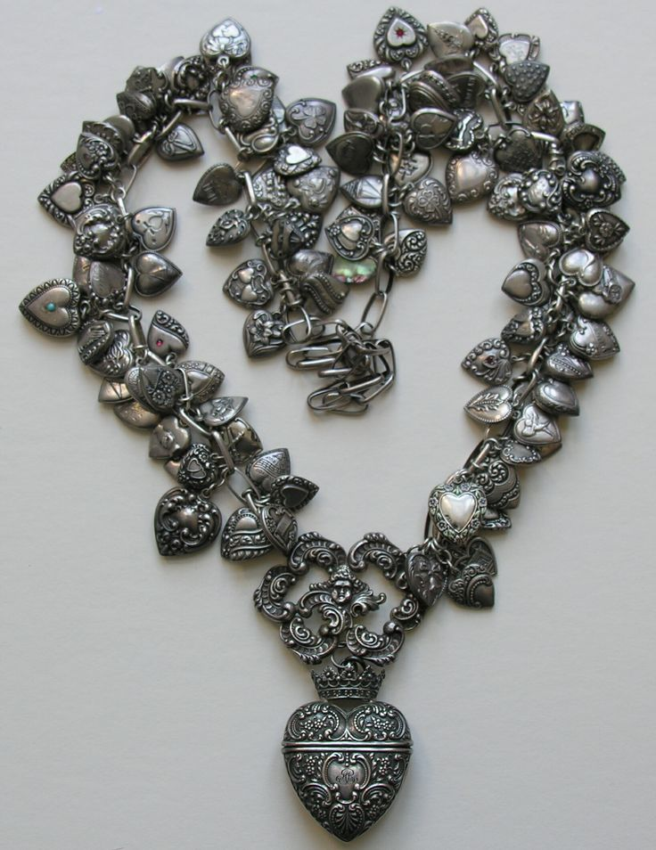 Collection of antique and vintage sterling hearts on a necklace.