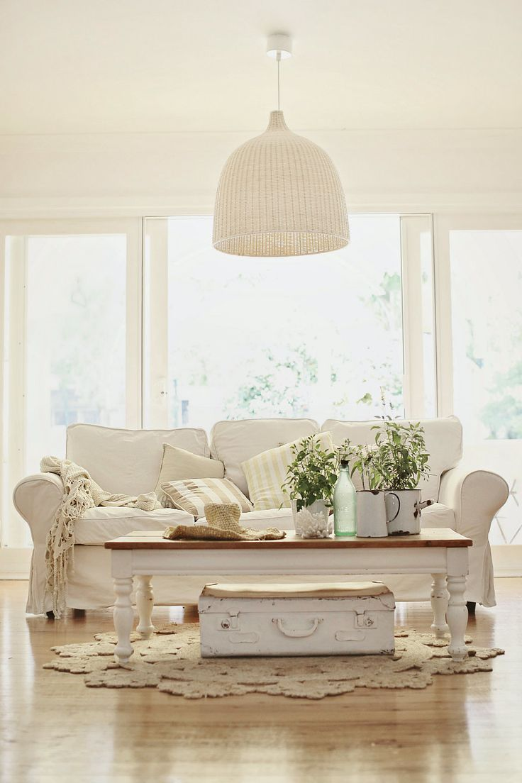 beachy coastal vintage style from http://abeachcottage.com wicker light, just rug, stripped floors, white slip-covered sofa, nautical stripe and old white painted suitcase
