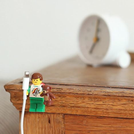 Lego Minifigures hacked with Sugru to create iPhone cable holders.