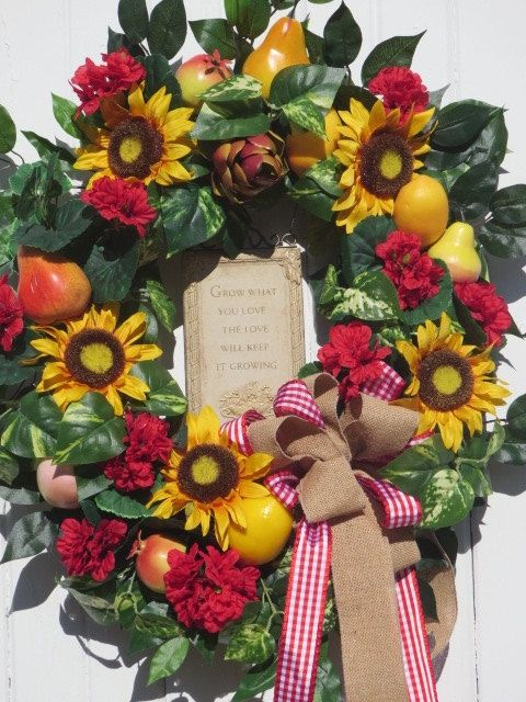 Farmhouse Garden Sunflower Fruit Wreath  The focal point of this country gardeners farmhouse wreath is a sone like plaque with the inspirational message: Grow what you will, and the Love will keep growing. An ideal message for the gardener in you!! The base is an 18 grapevine wreath to which I have added large yellow sunflowers, red geraniums and their foliage and a variety of fruit including lemons, pomegranates, pears, an apple and an artichoke. There is quite a bit of varied greenery…
