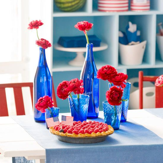 A collection of blue glass bottles and red flowers makes a fun  Australia Day centre piece