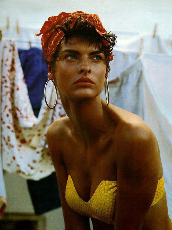 Model in yellow bikini head scarf and hoop earrings