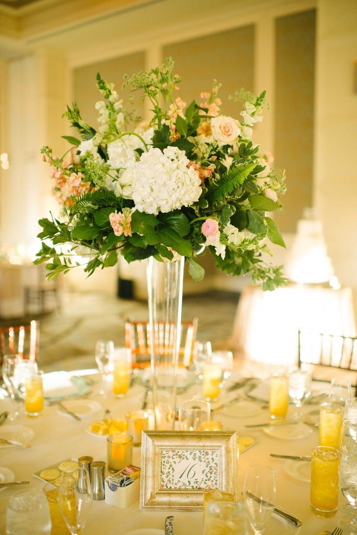 elegant ballroom tall reception centerpiece of pink ranunculus, white hydrangea, vendela roses, white snap dragons, white lisianthus, queen anne's lace, peach stock, fern, variegated pittosporum and lemon leaf on a clear glass trumpet vase.