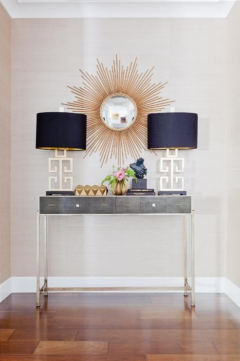 Gold and gray foyer features a gold sunburst mirror over a gray console table, Jonathan Charles Faux Anthracite Shagreen Console Table, topped with gold Greek lamps completed with black oval shades.