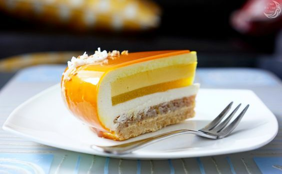 """Entremet cake """"Tropical Kiss"""" consists of coconut crumble, coconut dacquoise, mango creme, mango jelly & coconut mousse and is covered with the mirror glaze! I created this recipe thinking about tropical summer, light sea breeze, fresh mangos and coconut which is my favourite nut. I think it"""