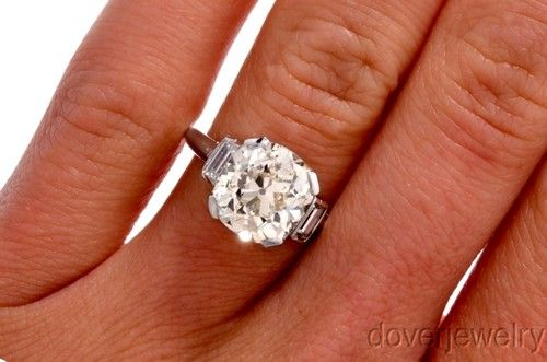 Antique Deco 4.95ct Cushion Cut Diamond Platinum Engagement Ring; the center diamond is graded at 4.30ct, K-L color, VS clarity & the 2 side baguettes are 0.65cttw, F-G color, VS clarity.  Currently up for auction on eBay.