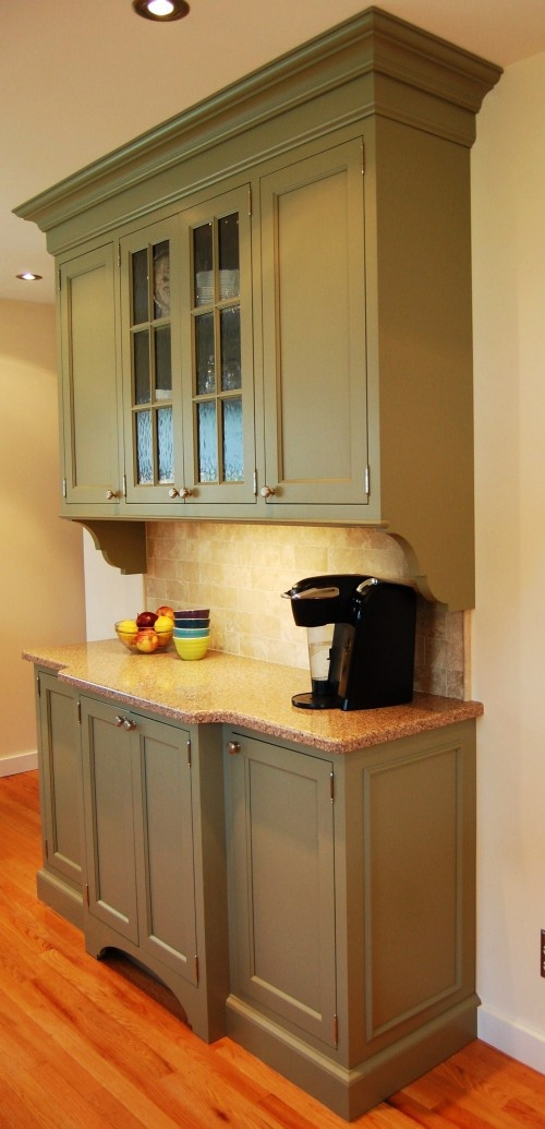 Sage cabinets with similar counter tops but different backsplash