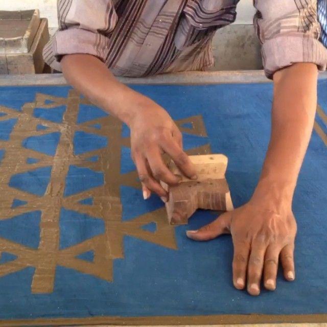 Process : Dabu (mud resist) being printed over indigo and sprinkled with…