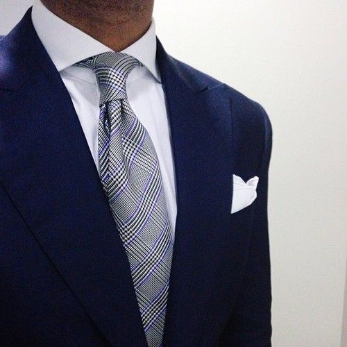 Prince of Wales check tie, white silk pocket square, a sharp cuttaway collar shirt and a classic navy suit. YES!