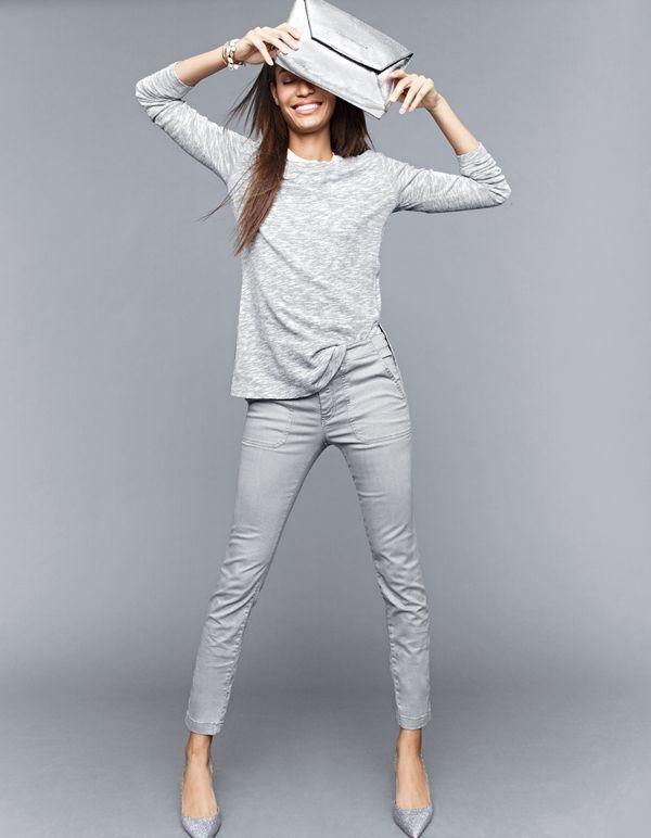 Grey sweatshirt with side slits, grey skinny pants, metallic envelope clutch, and  glitter d'Orsay pumps.