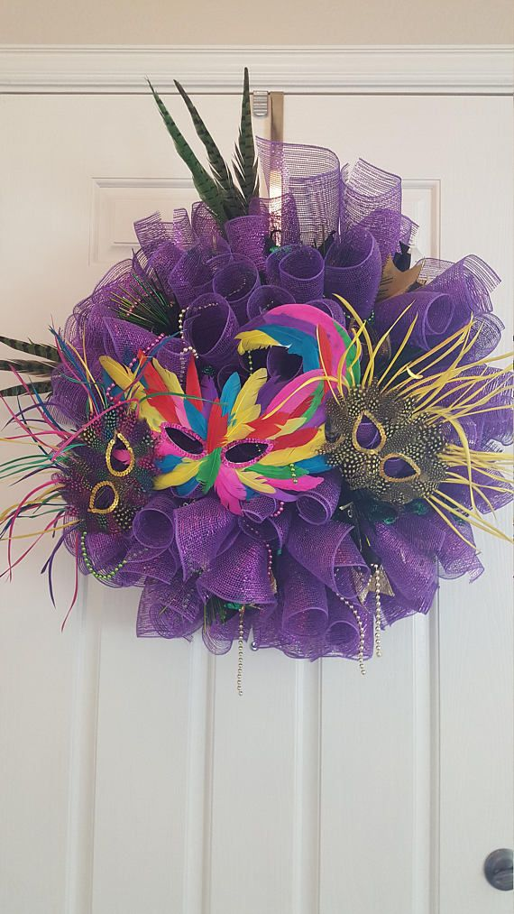 Full and vibrant homemade Mardi Gras wreath adorned with: Purple deco mesh Masks Beads Ribbons Feathers Depth is about 12 Width is about 26 Made on a 12 wire wreath form. Masks can be removed and replaced to change the look.