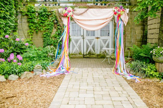 love the rainbow ribbons - and flowers! - in this ceremony backdrop