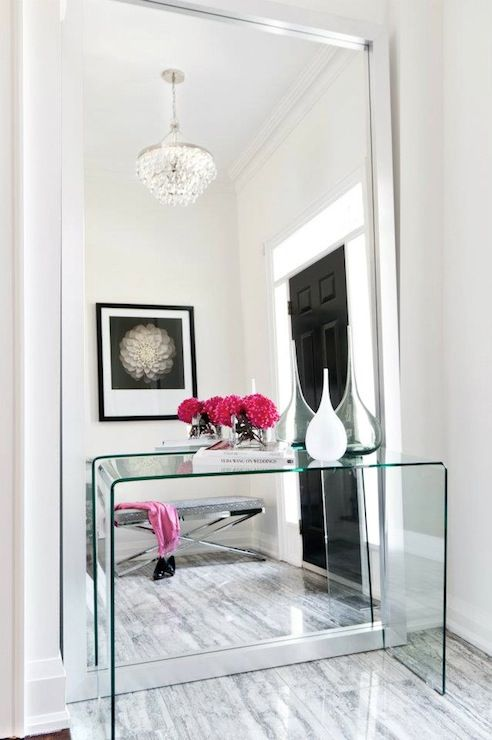 Lucite/ Glass Waterfall console paired with a leaning wall mirror. Don't forget the details: Hollywood Regency Chandelier + Chrome X-base Bench.