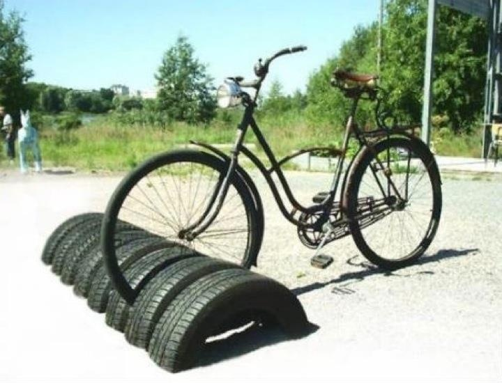 Used tires are half sunken in the ground for use as a clever bike rack.  Needs some more support though.