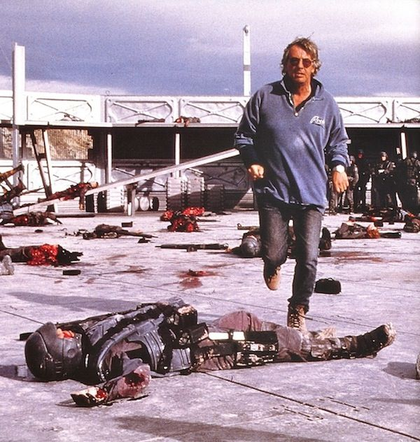 Paul Verhoeven nonchalantly stepping over bloody bits of human carnage on the set of Starship Troopers.