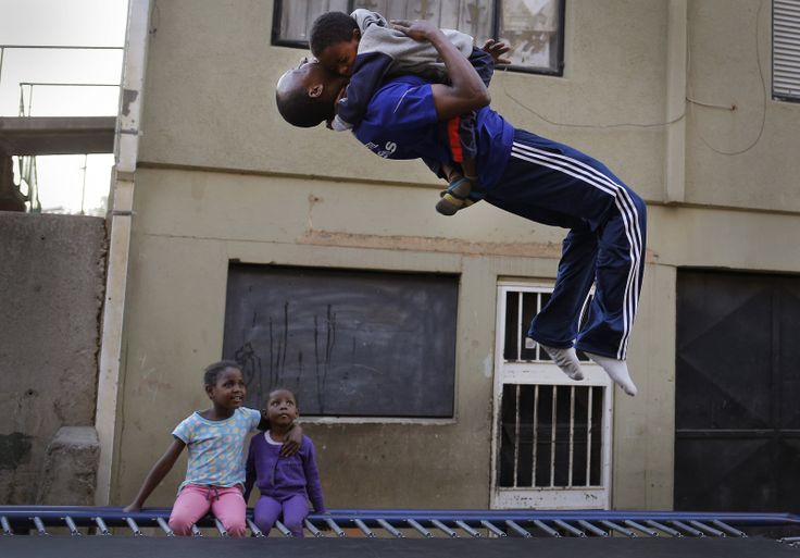 Xolani Nxumalo (19) holds a young boy as he jumps on a trampoline while children watch in the Alexandra township in Johannesburg, South Africa, June 24, 2014.