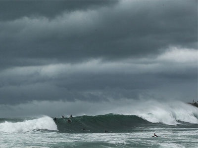 Surfers take on the large swells as storm clouds gather at Coogee Beach, NSW.