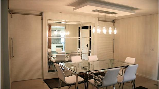 Sala de jantar com mesa de vidro e espelho composto chanfrado decorativo