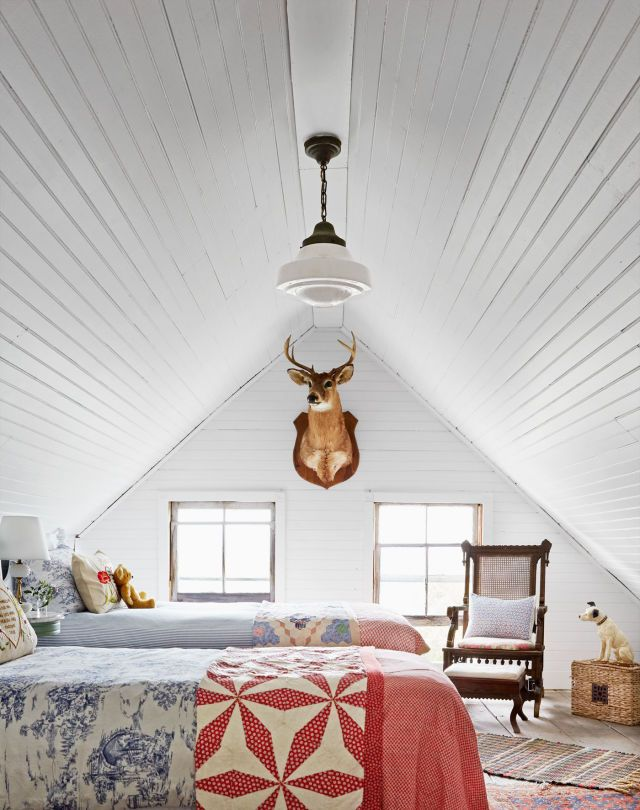 The spacious attic-turned- bunkroom houses five— five!—antique twin beds (two are shown). Mismatched quilts and layered rag rugs up the cozy factor.