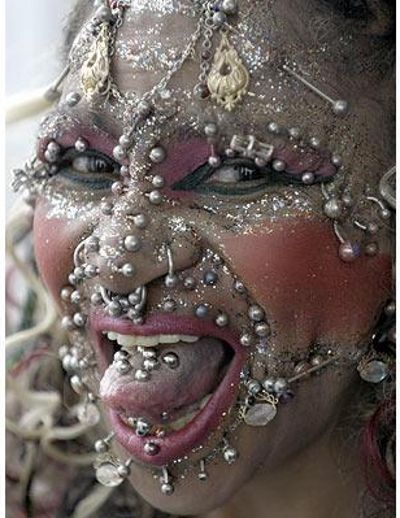 EWWW! The world's most pierced person is Brazilian born former nurse and current citizen of the UK, Elaine Davidson. Elaine began in the mid nineties with a modest collection of 250 piercings. By 2000 she had won her first world record with 462, reaching the 1000 mark in 2003, and continuing on at an amazing pace. Her last reported numbers from Summer of last year were absolutely staggering: over 6,700!