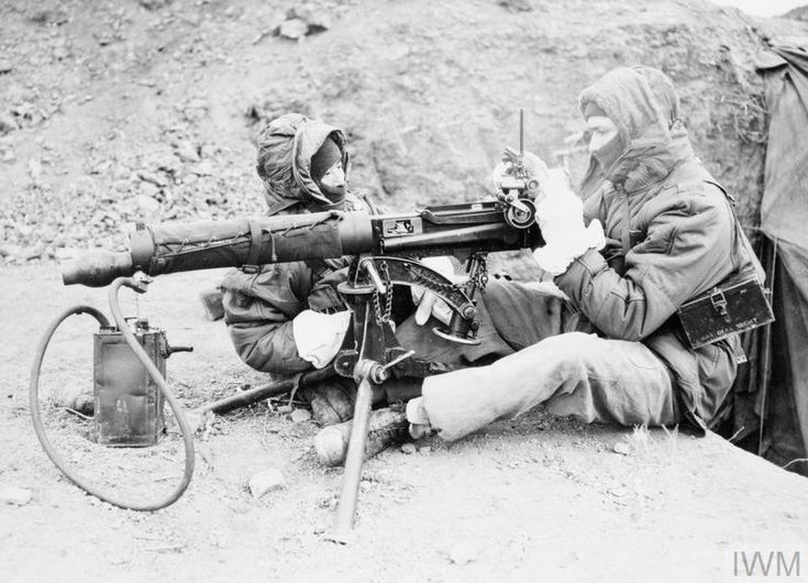 THE KOREAN WAR 1950 - 1953 British troops, wearing cold weather gear, test a Vickers machine gun before emplacing it.
