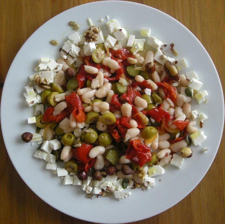 Para mediodía o cena. Ingredientes: - Alubias secas, crudas o en conserva. - olivas - pimiento rojo (para escalivarlo) - pepinillos en vinagre  - queso fresco (0% MG) - avellanas y nueces crudas - Semillas. - aceite de oliva virgen extra.