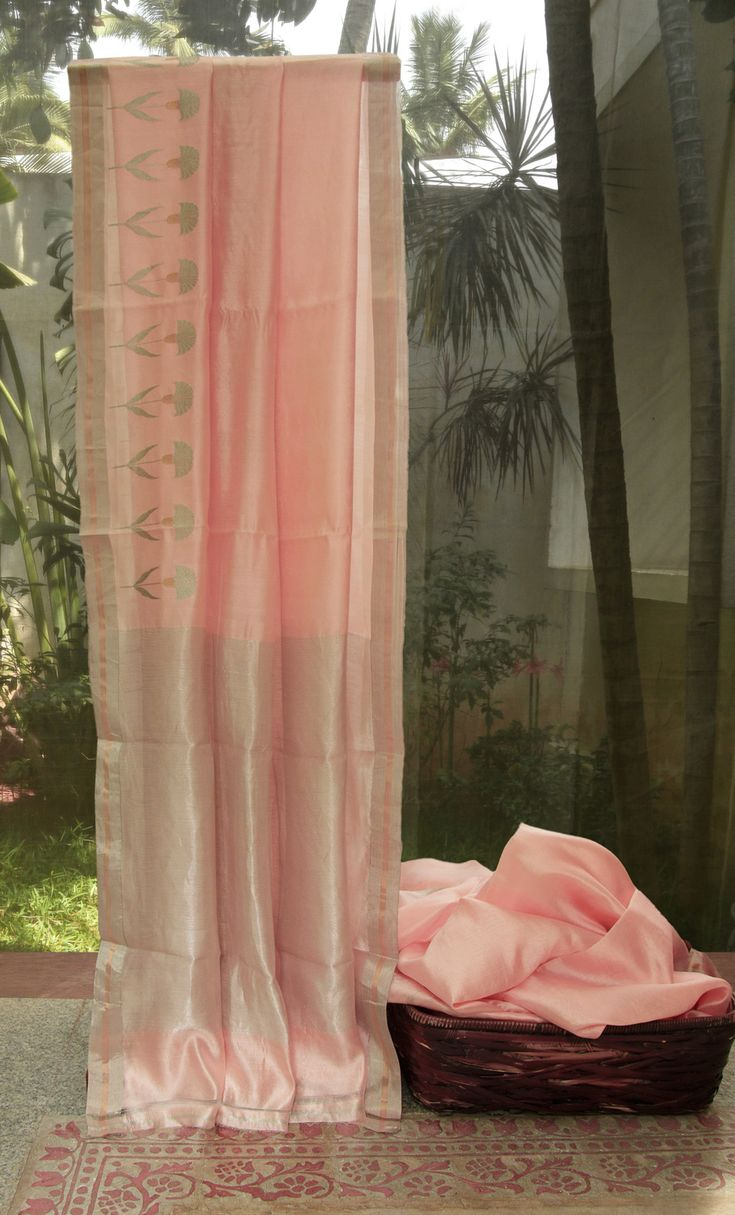 This bright chanderi silk is in peach color and has delicate florals woven along the border in silver zari with gold zari highlights. The contrasting border has bands in gold and silver zari. The p…