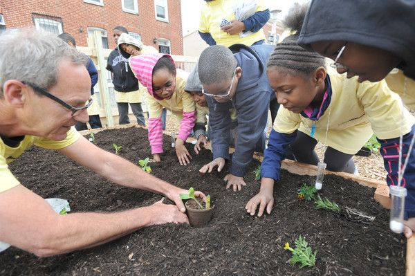 In the 500 block of Laurens St., Bill Dawson, far left, shows second graders from New Song Academy how to plant vegetables and flowers. More than 32 vacant city lots will be transformed into a community garden as part of The Scotts Miracle-Gro Company and The U.S. Conference of Mayors nationwide GRO1000 gardens and green spaces program.