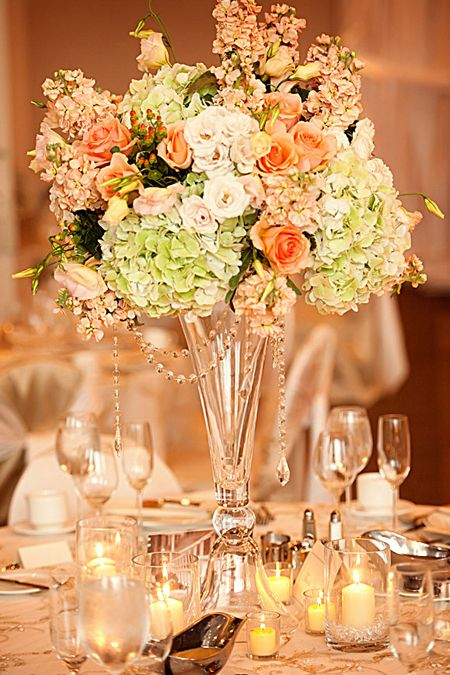 grapevine floral of Illinois centerpiece of green hydrangea, peach stock and peach roses centerpiece on a tall glass vase WITH PEARLS