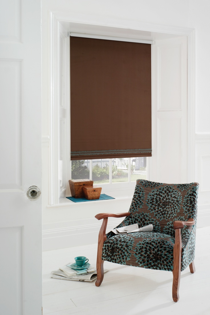 Plain brown roller blind with a duck egg braid in a white room with a brown and duck egg chair