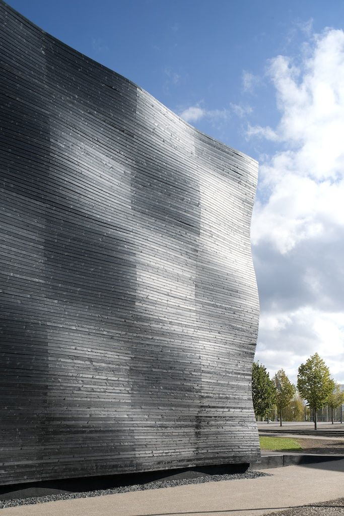 The facade consists of rough cut spruce planks. To counter the varying exposure to the weather and given the short time of service, the decision was made to coat the facade in black wood stain, so that the aging process is not visible. By offsetting the facade's substructure by one module the image of an undulating surface is created, which is shaped by the light.