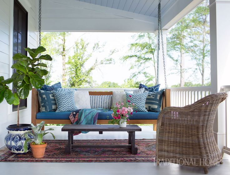 A large wraparound porch boasts multiple sitting areas. The designers chose a mix of textiles from local artisan Hable Construction for the porch swing. - Photo: Sarah Dorio / Design: Cloth & Kind