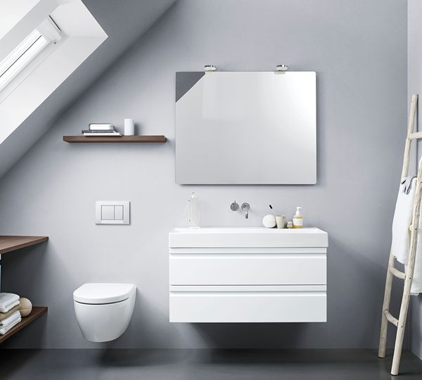 The integrated handles, the white washbasin and the classic mirror with stylish lights create a clean and nice look. Shelves and worktops in the new Lava colour use the space under the sloping wall.
