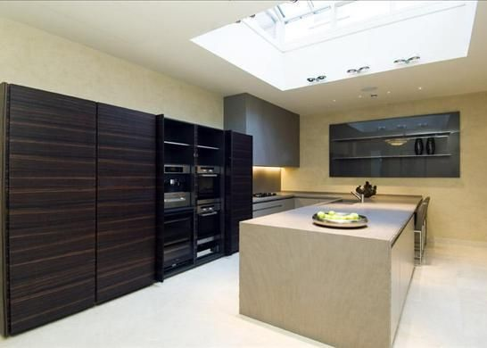 Minotti Atelier kitchen, Ebony tall units, matt lacquered base units with Light Brown Quartzite worktops, honed 60mm broken edge (the pocket doors are shown open, usually they would be closed over the appliances)