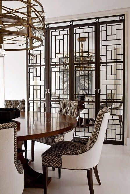 Dining Space - Beautiful round wood table with 2 tone upholstered dining chairs, gold metal chandelier with one imposing open grill room divider....now that is style!
