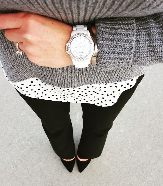 A gray sweater over a polka dot top with black pants and heels