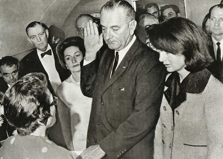 "Just hours after her husband's assassination, widow Jackie Kennedy stands next to Lyndon Johnson on Air Force One as he is sworn in as the 36th President of the United States. Although her personal assistant laid out a fresh change of clothes on her bed aboard the plane, Jackie refused to change out of her blood-spattered clothing saying, ""No, let them see what they've done."""