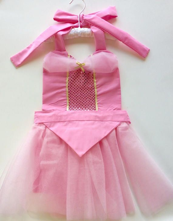 My Sleeping Beauty Tutu Princess Apron is fun for dress up, themed birthday parties, tea parties, helping mom and dad in the kitchen, or as a special gift.  This Aurora inspired costume is made with a perfectly pink tutu skirt over a pink apron skirt. It has a pink band that ties in the back. The heart shaped top is pink with middle section of pink sequin. Details of gold ribbon and a gold bow finishes the apron. Fits Ages 2 - 6  Please ask any questions, or for any special requests.  To…