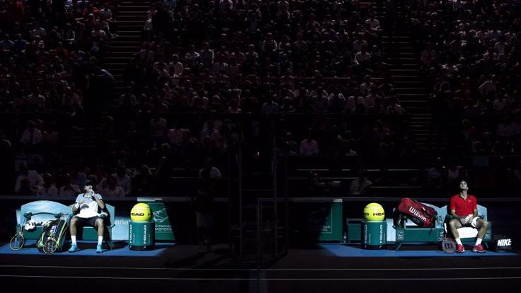 Tennissers Roger Federer (r) en Lucas Pouille pauzeren tijdens hun wedstrijd op het masterstoernooi in Parijs