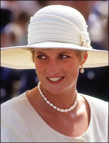 Princess Diana in July, 1991.  Princess Diana, wearing a single strand of cream pearls and pearl drop earrings. Diana's suit is by Catherine Walker and her hat is by Philip Somerville.