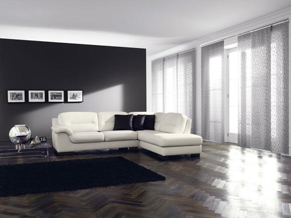 Composizione divano angolare in pelle bianca con 3 cuscini arredo neri.
