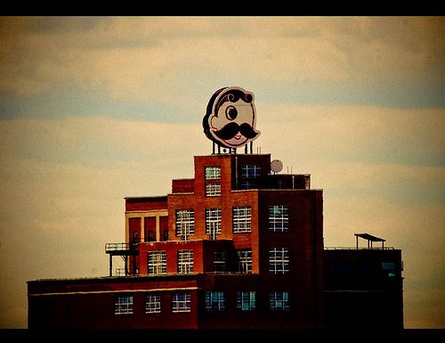 "Natty Boh Sign in Brewers Hill, Baltimore. National Bohemian, colloquially called Natty Boh, is an American beer originally brewed in Baltimore, Maryland, but now brewed by Miller Brewing in North Carolina and distributed by Pabst. First brewed in 1885 by the National Brewing Company (whose other brands were National Premium and Colt 45), this Bohemian-style beer's slogan has long been ""From the Land of Pleasant Living"" — a reference to the Chesapeake Bay."