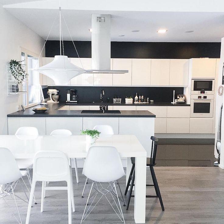 Mustavalkoinen sisustus yhdistää ruokailutilan keittiön tyyliin.
