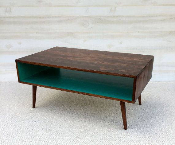 Coffee Table Mid Century Modern in Chery and Teal  Coffee Table Pictured L 40 x W 22 x H 18 or 16 Shelving Space: 6.5 x 22  Our handcrafted tables are custom made for each order. Mid Century Modern in style and made of homemade stains and Pine Select. This table is narrower than our standard tables and has angled legs without metal tips. If you prefer the metal tips, please message us! This coffee table is a custom order and will be shipped in 4-6 weeks of payment. Variations of colors are…